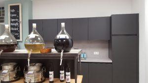 Eine antrazitfarbene Küche im Hintergrund, vorne Glasballons mit Essig und Öl