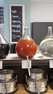 Glasballons mit Essigen und Ölen auf einem Tresen