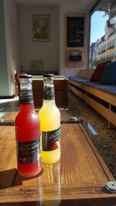 Zwei Saftflaschen mit Kronkorken auf einem Holztisch mit Glasplatte